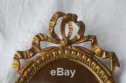 An antique French heavy bronze mirrored wall sconce, ribbon decoration